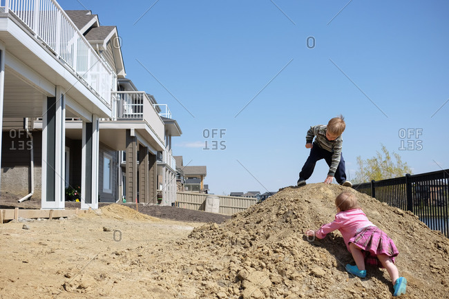 Two kids climbing a dirt mound in subdivision