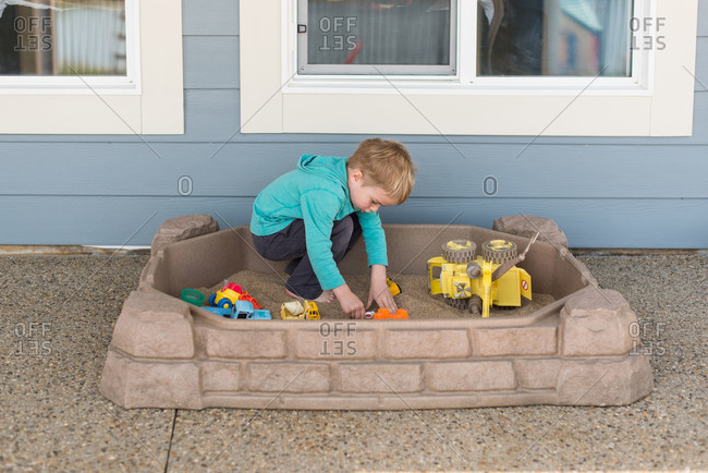 Little boy playing with vehicles in sandbox