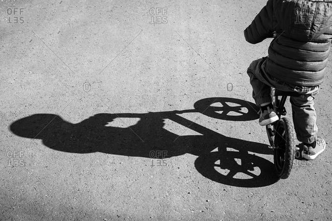 Long shadow of a boy on his bike