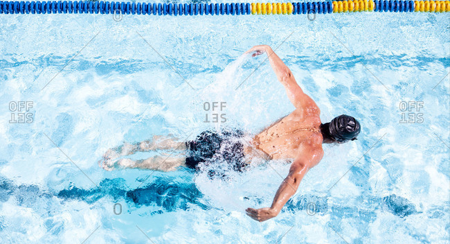 A swimmer spreading his arms to do the breaststroke in a pool