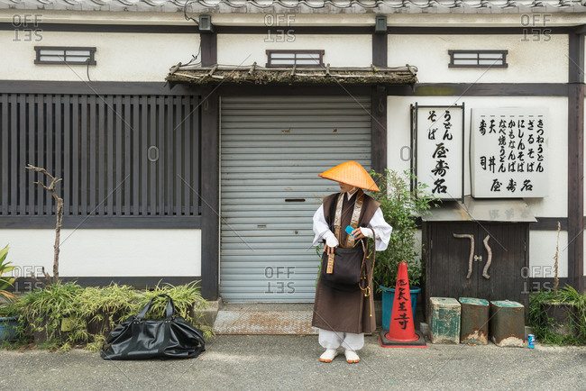 September 5, 2015:  Woman in a woven bamboo hat stands outside a shuttered business