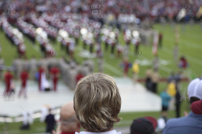 A spectator watches a halftime show on a football field