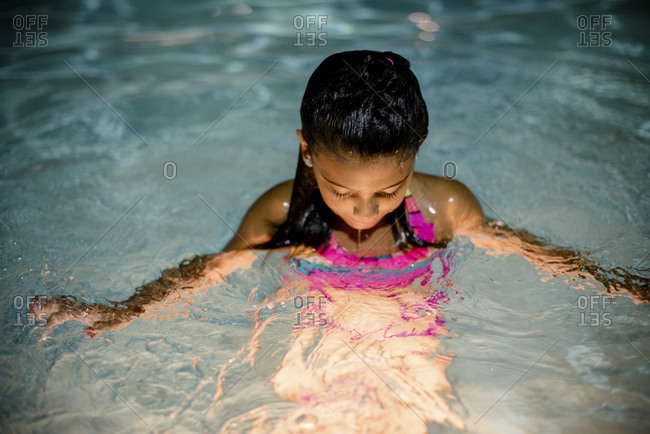 A girl in a pool at night