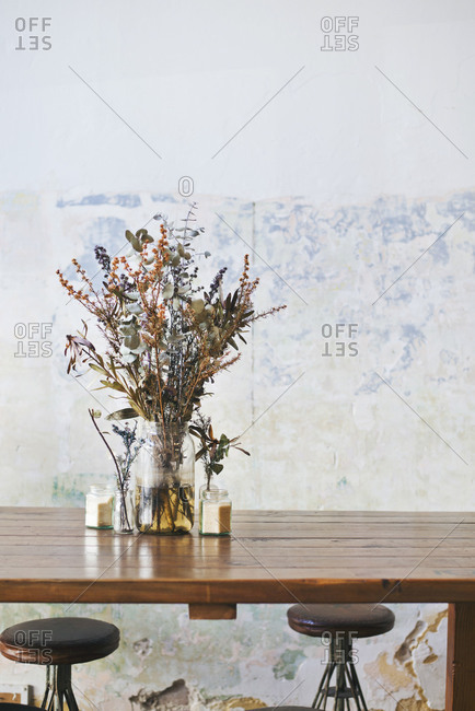 A vase of dried flowers on a countertop