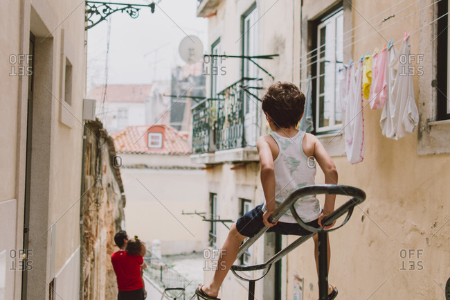 Young boy playing on stair railing between buildings in European hillside village