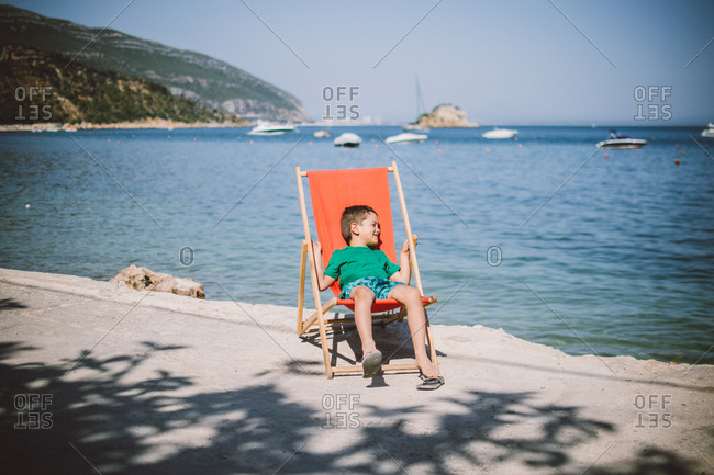 Terrific Young Boy Lounging In Beach Chair On Coastal Walkway Stock Ocoug Best Dining Table And Chair Ideas Images Ocougorg