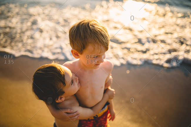 Two brothers hug at a beach