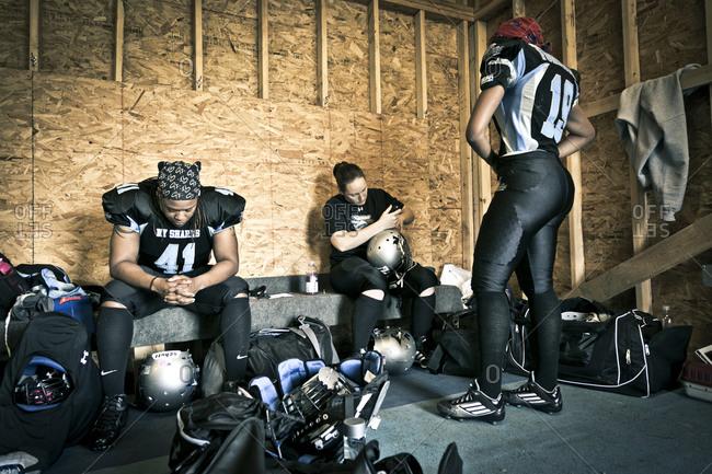 Brooklyn, New York, USA - April 19, 2014: Women preparing for a football game in a locker room