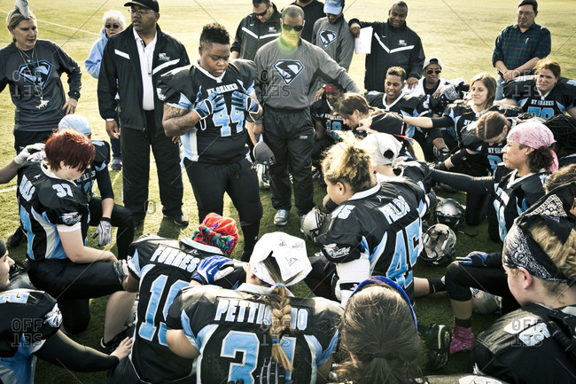 Brooklyn, New York, USA - April 19, 2014: Women's football team huddling together before a game