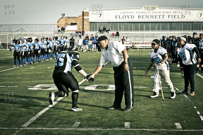 Brooklyn, New York, USA - April 19, 2014: Female football player slapping an official's hand before a game