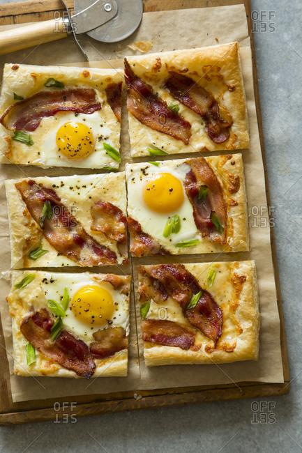 A breakfast tart with eggs, bacon, green onion