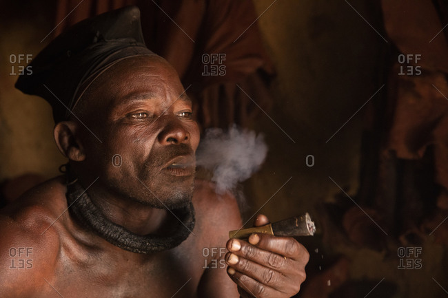 Himba man smoking bullet shell pipe