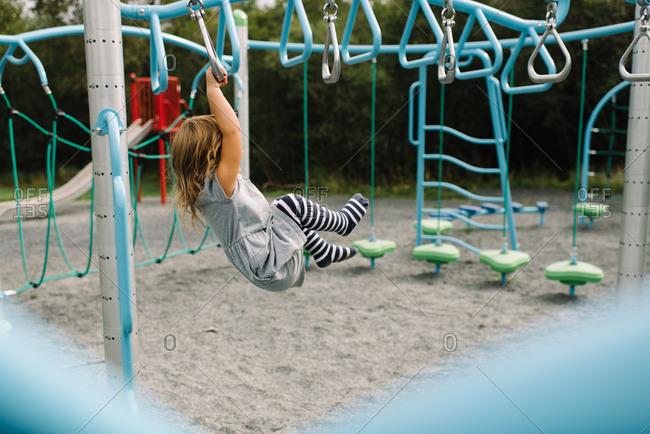 Little girl dangling from monkey bars