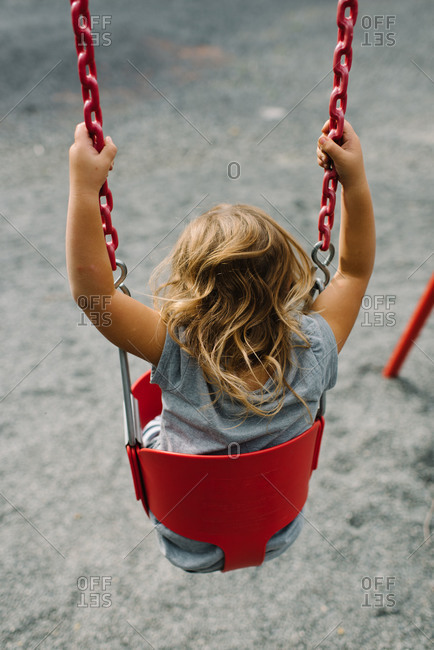 Girl sitting in playground's baby swing