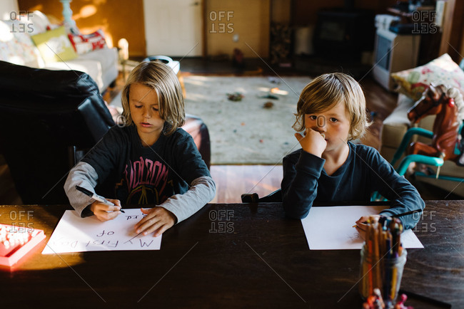 Two boys together writing notes about school