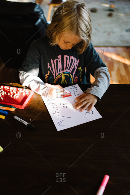 Boy at a table writing notes about school