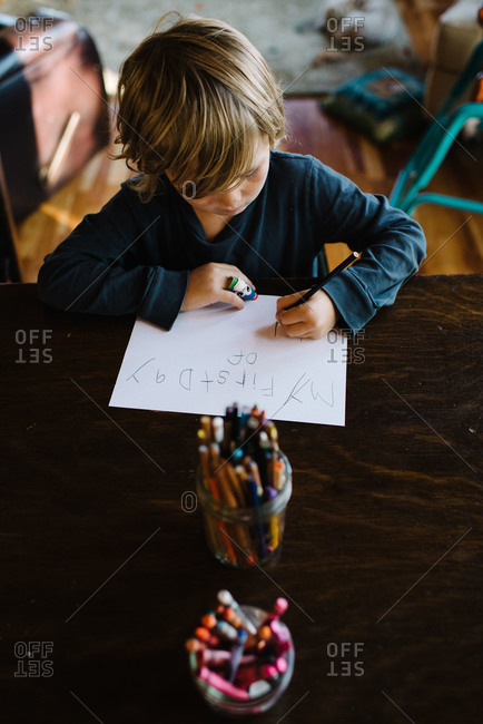 Boy at table writing notes about school