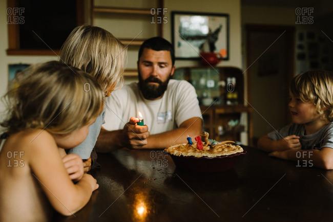 Dad and kids around a birthday pie