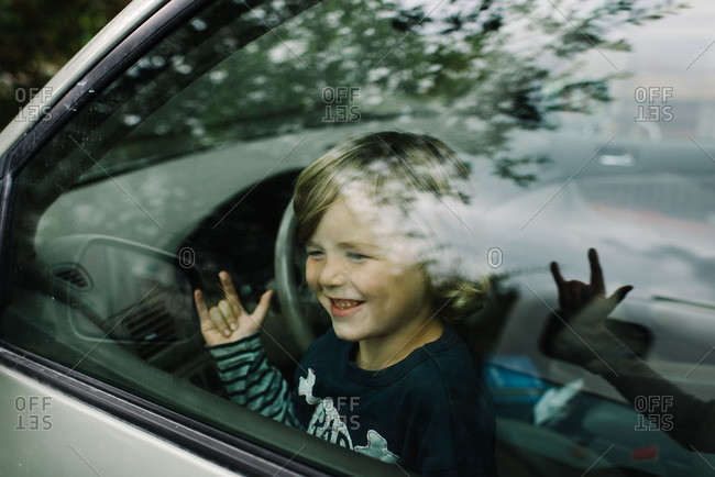 Boy making love sign in car window
