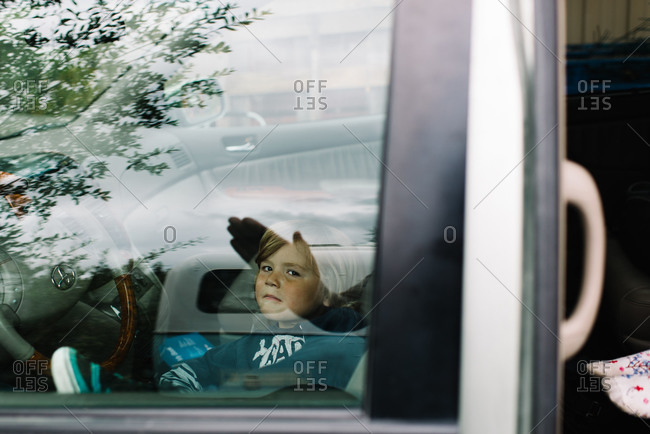 Boy in car window with reflection of hand waving