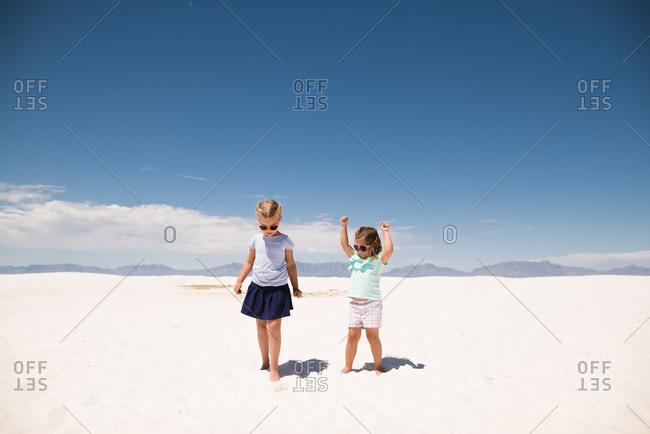 Little girls standing on white sand, White Sands National Monument in Alamogordo, New Mexico