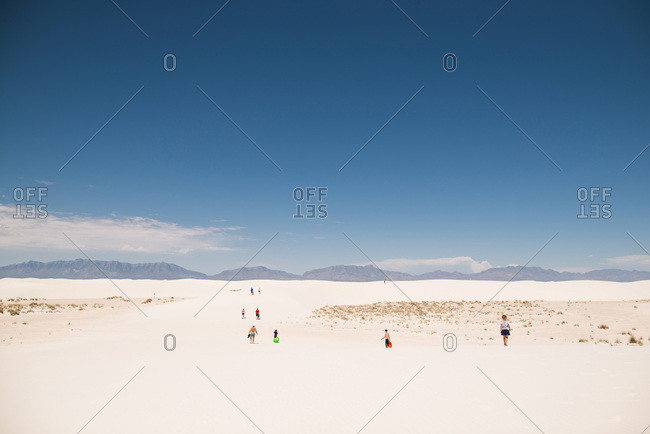 People walking across white sand dunes, White Sands National Monument in Alamogordo, New Mexico