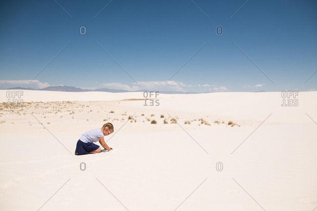 Little girl playing in white sand, White Sands National Monument in Alamogordo, New Mexico