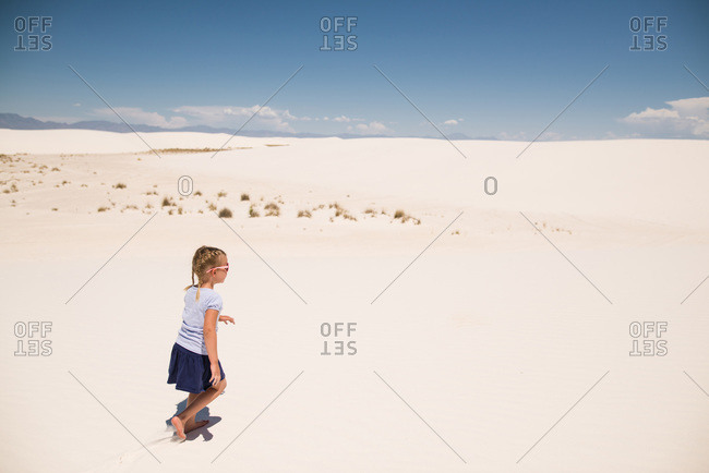Girl walking across white sand dunes, White Sands National Monument in Alamogordo, New Mexico