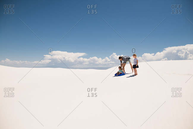 Father and daughters playing on white sand dunes, White Sands National Monument in Alamogordo, New Mexico