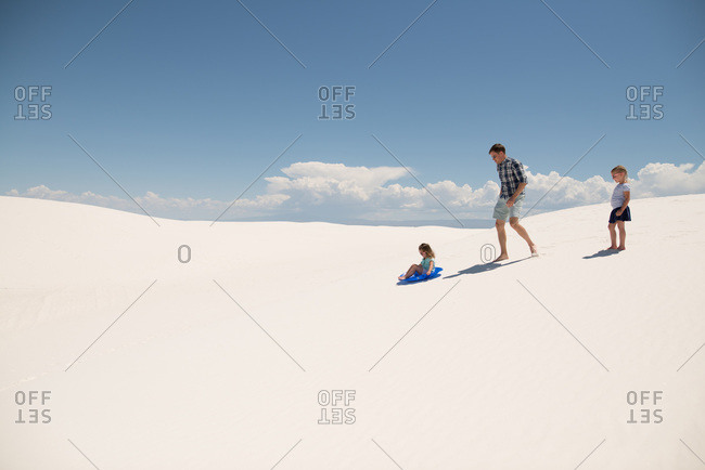 Father and his two girls playing on white sand dunes, White Sands National Monument in Alamogordo, New Mexico