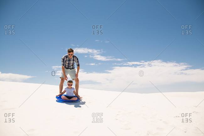 Girl in a sled being pushed by her father on a white sand dune, White Sands National Monument in Alamogordo, New Mexico