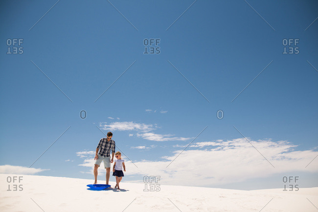 Father and daughter with a sled on white sand dunes, White Sands National Monument in Alamogordo, New Mexico