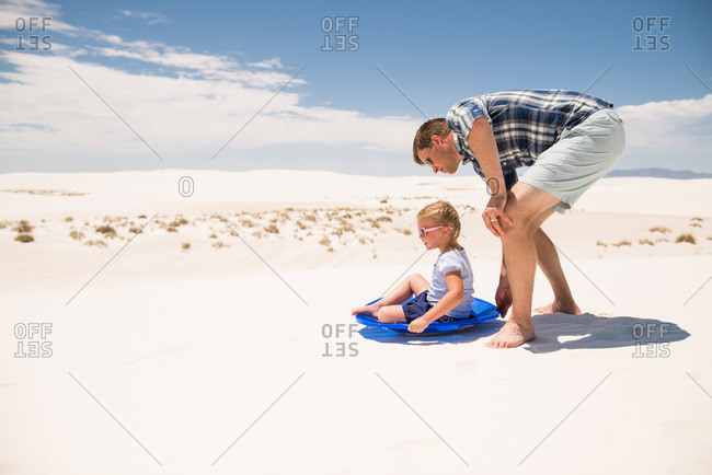 Man pushing his daughter in a sled on white sand dunes, White Sands National Monument in Alamogordo, New Mexico