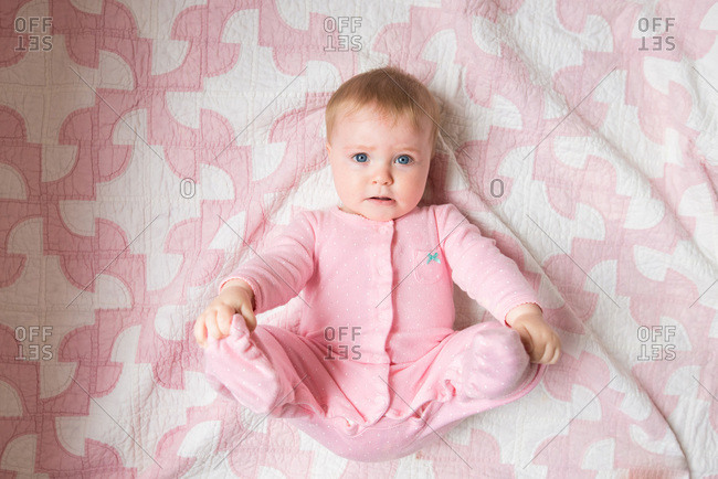 Portrait of a baby girl lying on a pink and white quilt