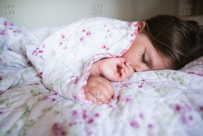 Little girl wrapped in a quilt sleeping