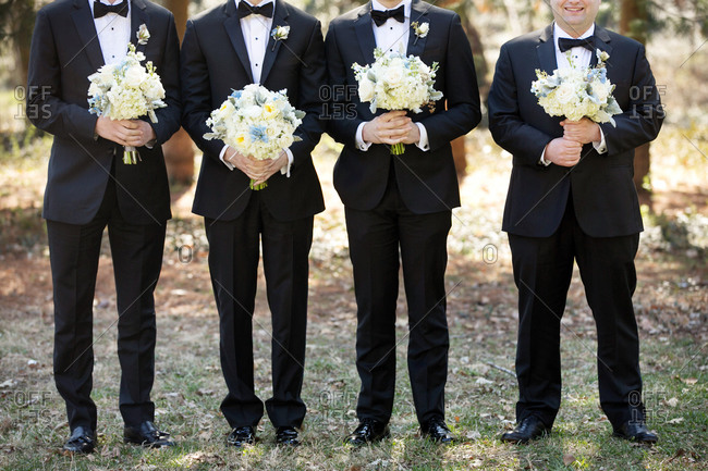 Neck down shot of four groomsmen in tuxedos holding bouquets of flowers