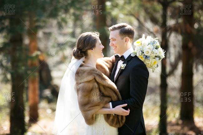 Waist up portrait of bride and groom standing in woods