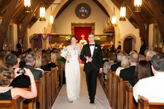 Bride and groom walking down the center aisle of church after ceremony