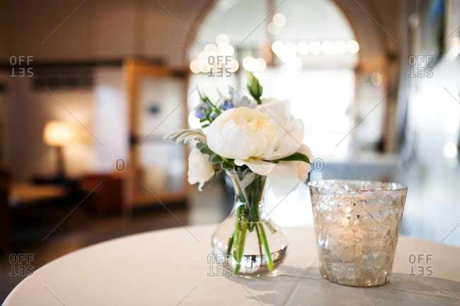 Close-up of white flowers in vase and votive candle on table in banquet hall