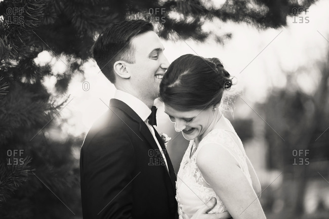 Close bride and groom laughing under pine boughs at dusk