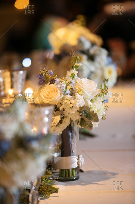 Flower arrangements on long banquet table at wedding reception