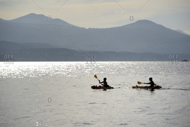 Two kids kayaking in front of Vancouver Island