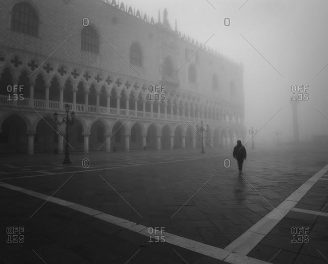 Man walking in Piazza San Marco in morning fog, Venice