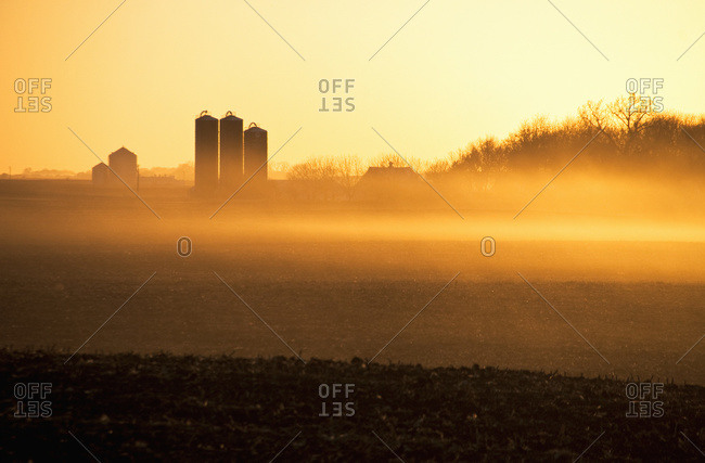 Hazy sunrise light on fallow cornfields and a farmstead with Harvestore silos, near Truman Minnesota, USA