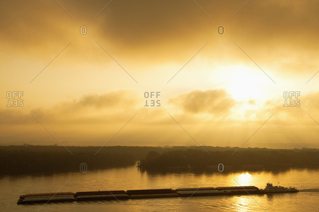 Grain barge navigating the Mississippi River in early morning light, near Hannibal, Missouri, USA