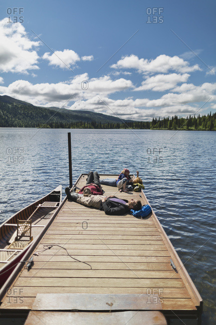 Three adults and a young girl lounging on a boat dock on a lake soaking up the sun, Byers Lake campground, Denali State Park, Alaska, United States of America
