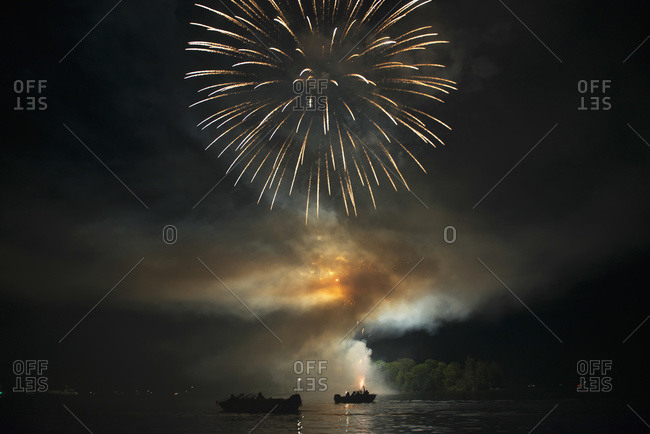 Fireworks display over a lake illuminating the boats on the water, Kenora, Ontario, Canada