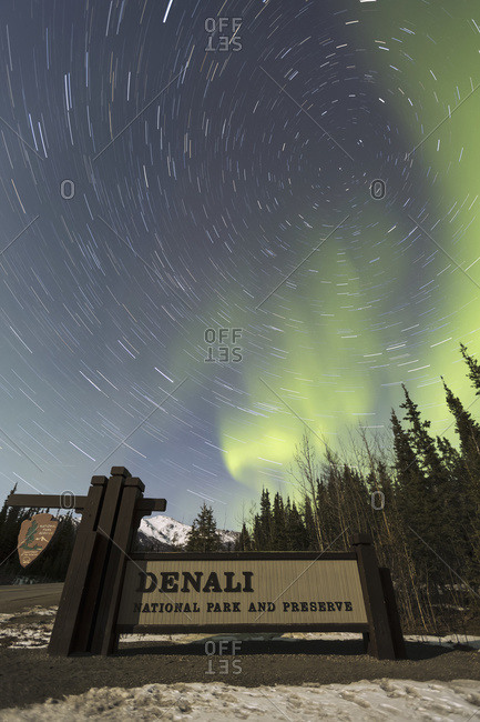 The Aurora Borealis (Northern Lights) and stars circling above the sign marking the entrance to Denali National Park and Preserve, Alaska, United States of America