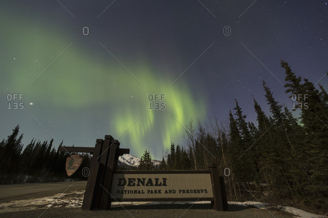 The Aurora Borealis (Northern Lights) dancing above the sign marking the entrance to Denali National Park and Preserve, Alaska, United States of America