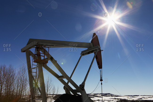 Pumpjack and snow covered hills with sun burst and blue sky, Longview, Alberta, Canada